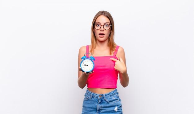 目覚まし時計を保持している赤い頭のきれいな女性 Premium写真