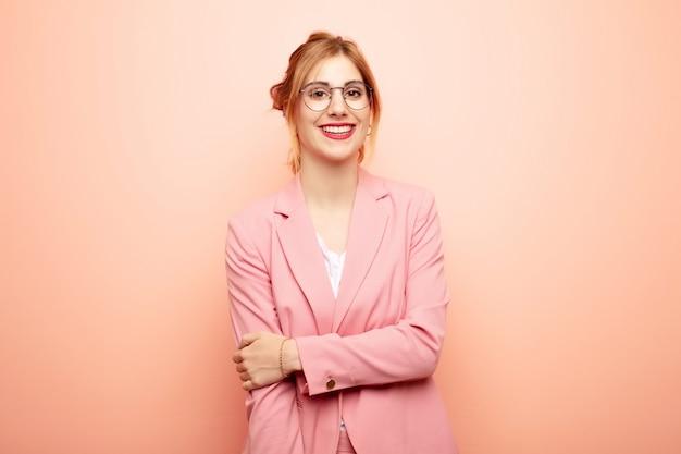Молодая симпатичная блондинка смеется застенчиво и весело, с дружелюбным и позитивным, но неуверенным отношением Premium Фотографии