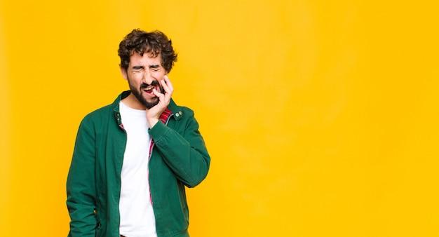 頬を保持し、痛みを伴う歯痛に苦しんでいる若い狂気のひげを生やした男 Premium写真