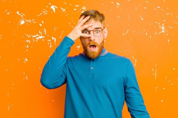 Молодой рыжеволосый мужчина выглядит шокированным, напуганным или испуганным, закрывая лицо рукой и заглядывая между пальцами на оранжевую гранжевую стену Premium Фотографии