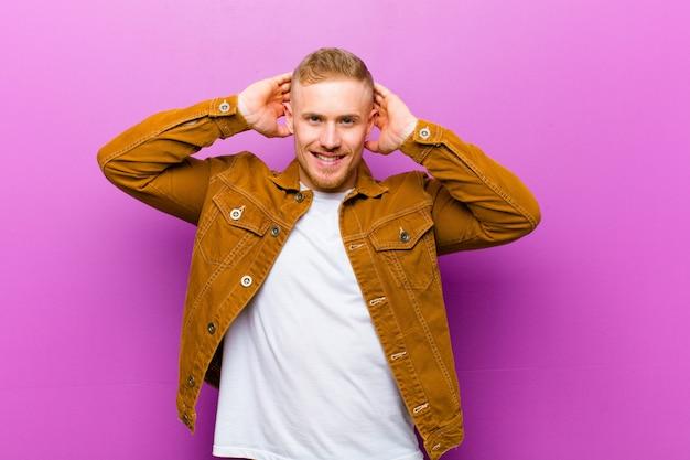 Молодой блондин, выглядящий счастливым, беззаботным, дружелюбным и расслабленным, наслаждающимся жизнью и успехом, с позитивным отношением к фиолетовой стене Premium Фотографии