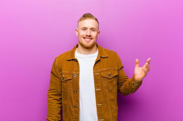 Молодой блондин, чувствуя себя счастливым, удивленным и жизнерадостным, улыбаясь позитивным настроем, осознавая решение или идею на фоне фиолетовой стены Premium Фотографии