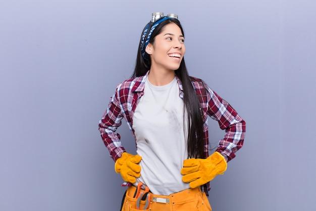 幸せ、陽気、自信を持って、誇らしげに笑って、腰に両手で側を探している若いラテン女性 Premium写真