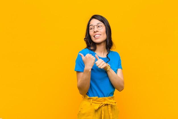 陽気にそしてさりげなく側にコピースペースを指して、オレンジ色の壁に満足して満足している感じ笑顔若いかなりラテン女性 Premium写真