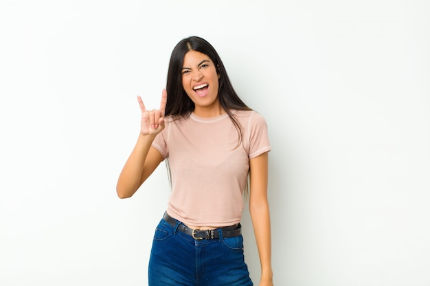 若い可愛いラテン女性の幸せ、楽しい、自信を持って、前向きで反抗的、フラットな壁に手でロックまたはヘビーメタルサインを作る Premium写真