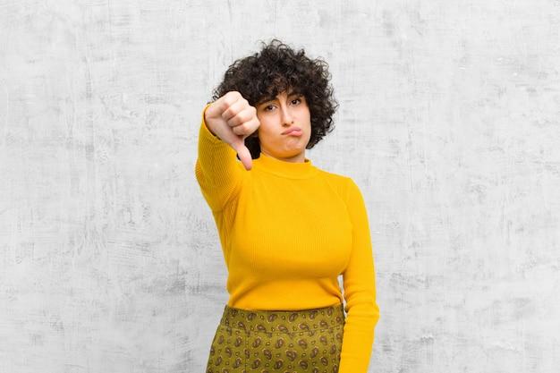 若いかなりアフロの女性のクロス、怒り、イライラ、失望、または不快感、深刻な表情で親指を下に見せている Premium写真