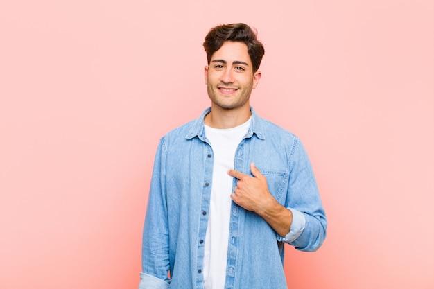 Молодой красавец выглядит счастливым, гордым и удивленным, весело указывая на себя, чувствуя себя уверенно и возвышенно над розовой стеной Premium Фотографии