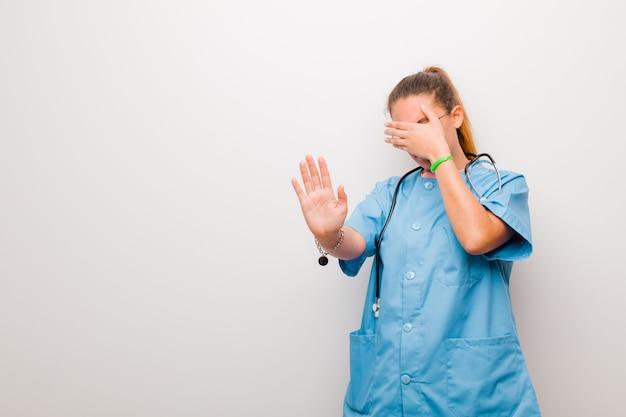 Молодая медсестра закрыла лицо рукой и положила другую руку вперед, чтобы остановить камеру, отказываясь от фотографий или картинок на белой стене Premium Фотографии