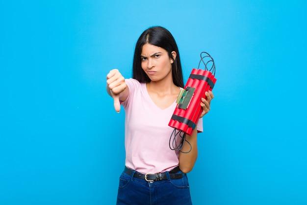 若い可愛いラテン女性のクロス、怒り、イライラ、失望、または不快感を感じ、平らな壁に真剣な表情で親指を下に見せて Premium写真