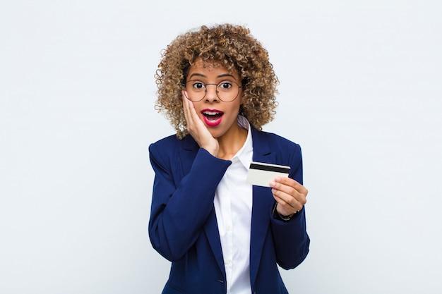 Молодая афроамериканская женщина чувствует себя шокированной и испуганной, выглядит испуганной с открытым ртом и руками на щеках с помощью кредитной карты Premium Фотографии