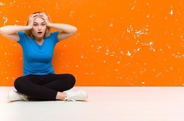 恐怖とショックを受けた若いブロンドの女性、頭に手を上げると床に座っている間違いでパニックに陥る Premium写真