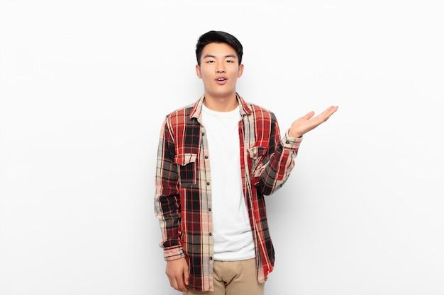 Молодой китаец, чувствующий себя счастливым, удивленным и веселым, улыбающимся с позитивным настроем, реализующим решение или идею на фоне плоской цветной стены Premium Фотографии