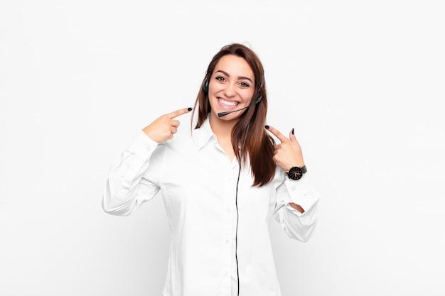 Молодая симпатичная женщина, уверенно улыбающаяся, указывая на собственную широкую улыбку, позитивное, расслабленное, довольное отношение с наушниками и микрофоном Premium Фотографии