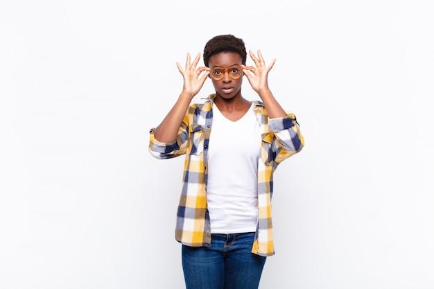 ショックを受け、驚き、驚き、驚いた、信じられないような表情でメガネを握る Premium写真