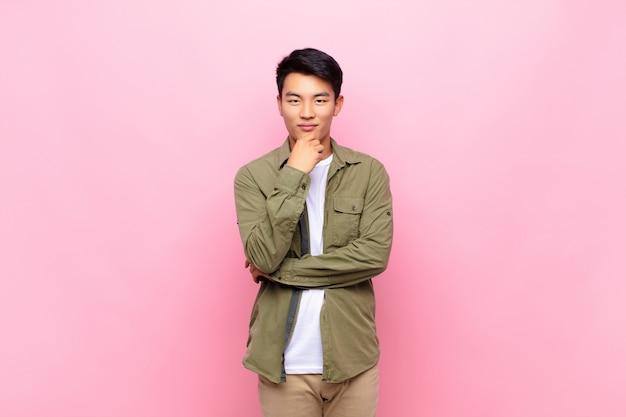 Выглядит счастливым и улыбается рукой на подбородке, задается вопросом или задает вопрос, сравнивая варианты Premium Фотографии