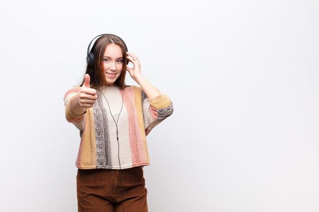 Музыка молодой белокурой девушки слушая с наушниками против белой стены Premium Фотографии