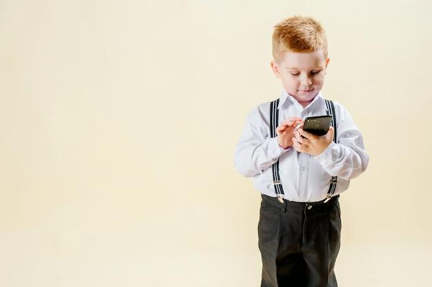 Маленький рыжий мальчик в деловом костюме с телефоном в руке спешит на встречу в деловом костюме, бизнес, мини-босс Premium Фотографии