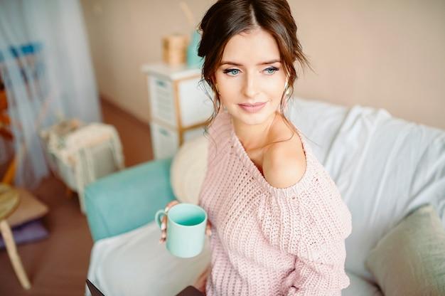 ヨーロッパの外観の美しい若い女の子は、彼女の手に打撲マグで居心地の良い家庭環境に座っています Premium写真