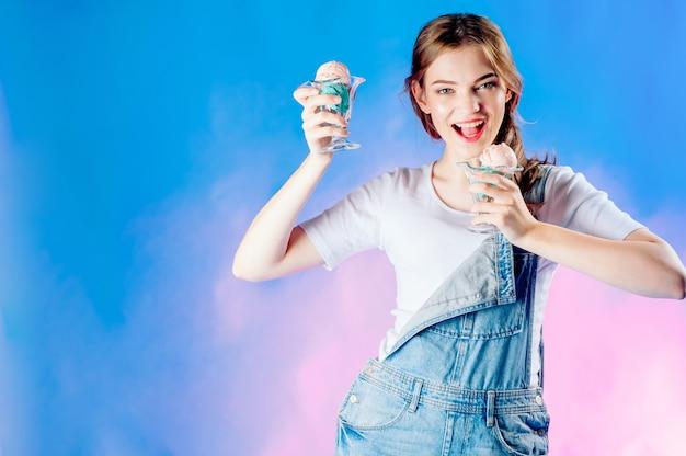 青の美しい感情的な女の子は、彼女の手でおいしいピンクアイスクリームを保持しています。甘い販売、販売 Premium写真