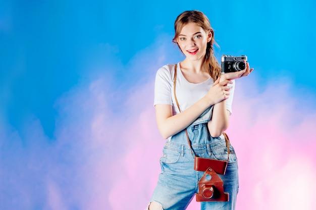 休暇に行く青色の背景にカメラでスーツケースの女の子 Premium写真