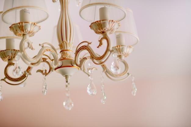 Красивый желтый и синий свет, отражающийся сквозь матовые чешские стеклянные кристаллы, висящие на старинной люстре Premium Фотографии