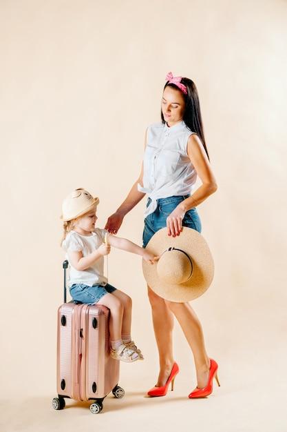 Отправляйся в приключение. счастливая семья готовится к путешествию. мама и дочка пакуют чемоданы для поездки. Premium Фотографии