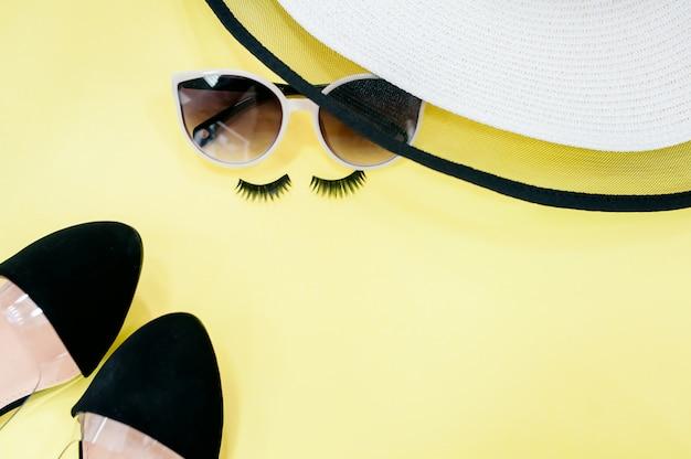 日光とココナッツの葉の影と黄色の背景にトップビュー帽子とサングラス。 Premium写真