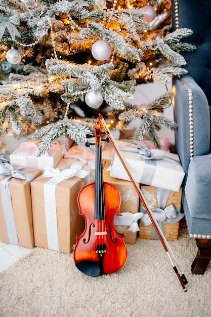Скрипка возле новогодних подарков Premium Фотографии
