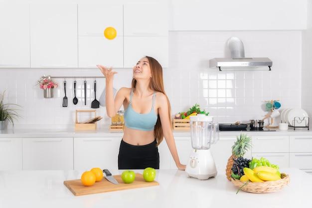 フィットネス女性がキッチンでジュースのスムージーを調理します。 Premium写真