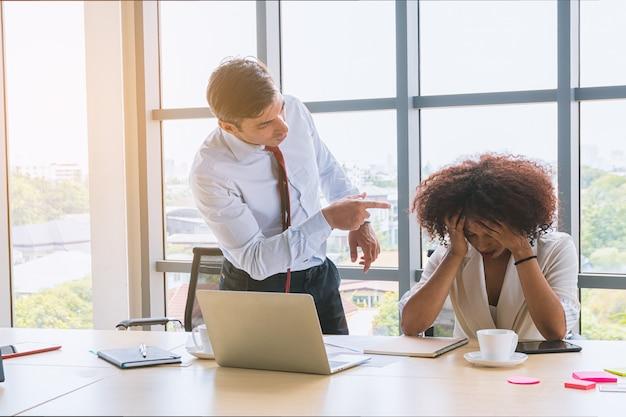 上司としてのビジネスマンは彼の従業員を非難し、警告します。 Premium写真