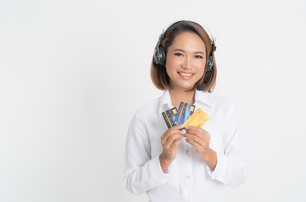 Центр телефонного обслуживания женщины с удерживанием шлемофона и кредитной карточкой. Premium Фотографии
