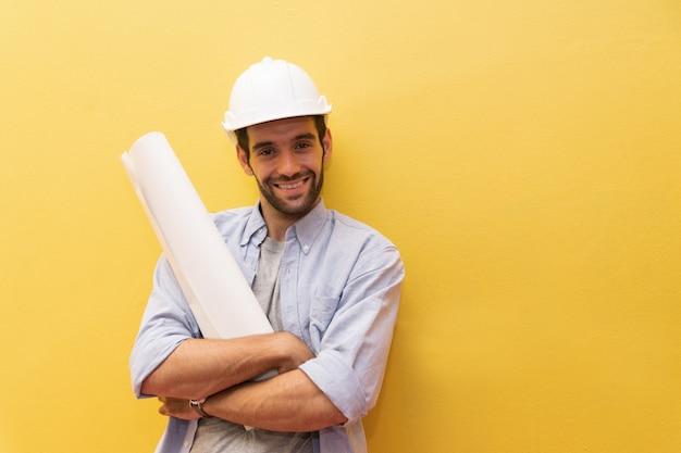 黄色の背景にエンジニアの男の肖像画。 Premium写真