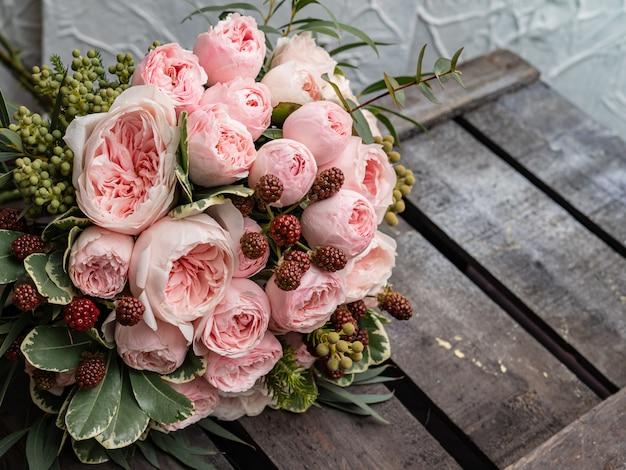 低木と牡丹の優しいピンクのバラの美しいウェディングブーケ。 Premium写真