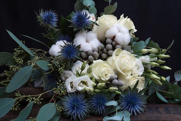 Зимний свадебный букет из белых роз, хлопка и эрингиума на черном. букет невесты. Premium Фотографии