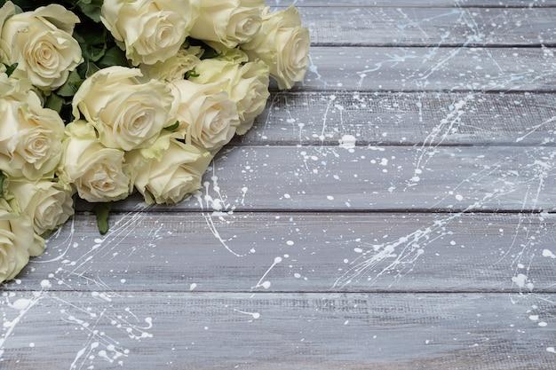 Белые розы на сером фоне деревянных. копировать пространство Premium Фотографии