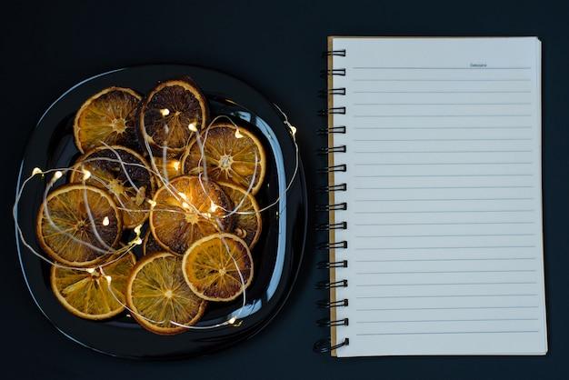 Тарелка с кусочками сушеного апельсина и горящей гирляндой с пустой записной книжкой Premium Фотографии