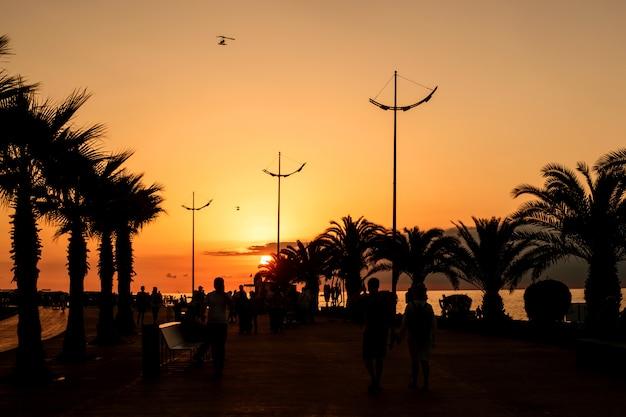 リゾート都市バトゥミのジョージア州の黒海で休息。海の遊歩道に沈む夕日。 Premium写真