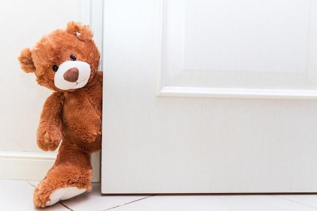 Мишка за открытой дверью. дети играют с мягкой игрушкой. скопируйте место на белой двери. Premium Фотографии