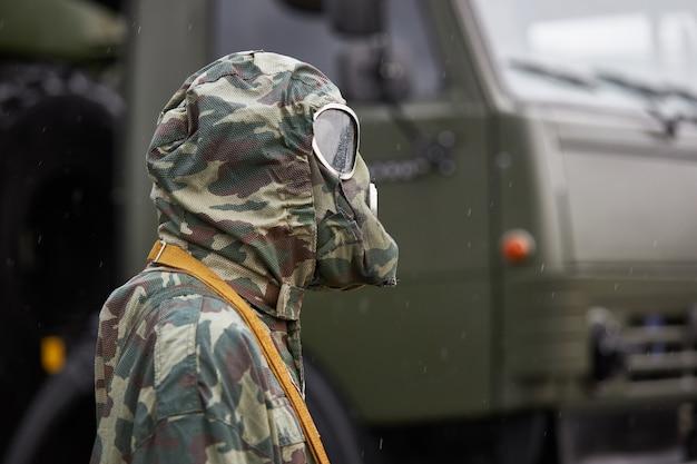 Манекен, одетый в специальный камуфляжный костюм химической защиты и противогаз, стоит на военном грузовике Premium Фотографии