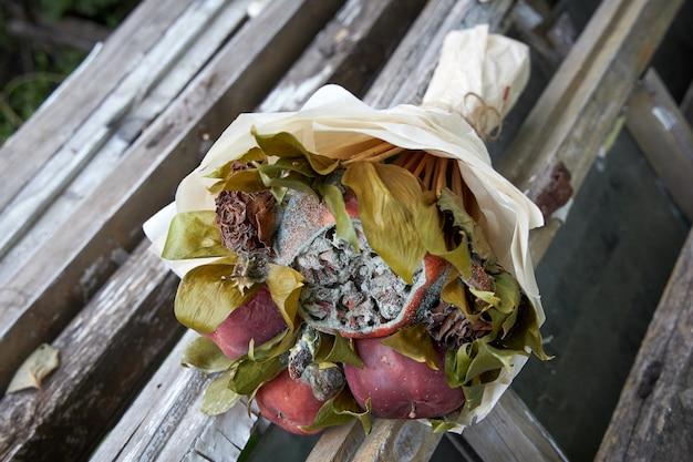 壊れた木造家屋の遺跡にある腐った果物としおれた花の花束 Premium写真