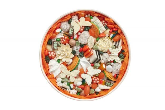 Круглая коробка с оранжевыми конфетами и шоколадом ручной работы, изолированная на белом Premium Фотографии