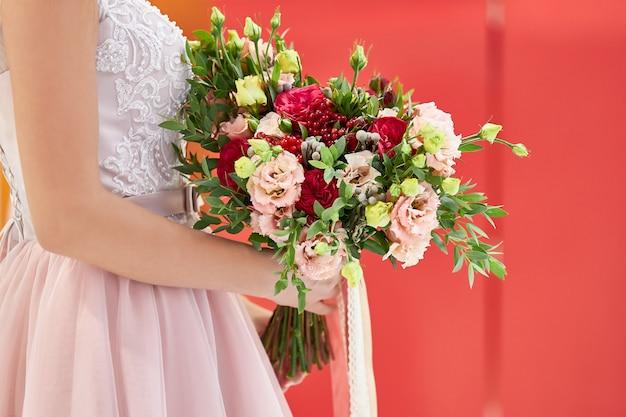 ピンクのドレスを着た花嫁は、カーネーションとバラの美しい花束を持って立っています。 Premium写真