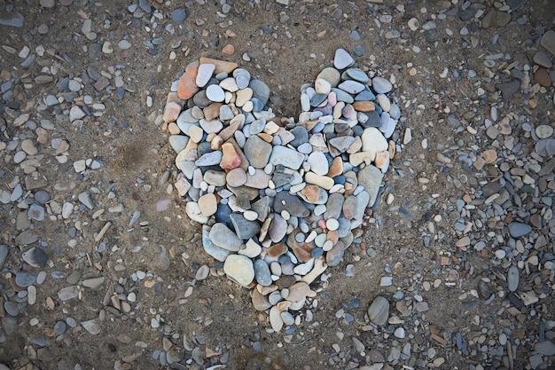 Большое сердце из мелкой гальки на берегу моря Premium Фотографии