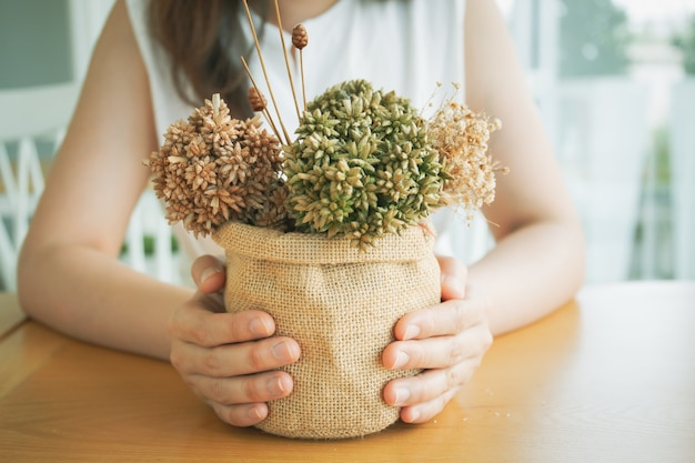 彼女のビンテージコーヒーバーで花の花束を飾る美しい少女をクローズアップ。 Premium写真