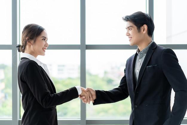 ビジネスマンやビジネスウーマンのビジネストークの後に握手をしています。プロのビジネス人々の概念。 Premium写真