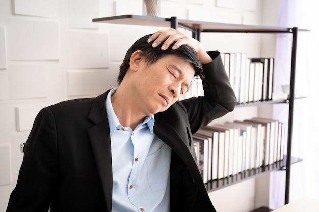 У азиатского старшего делового человека есть проблема офисного синдрома от трудолюбия. здравоохранение и работа концепции баланса жизни в трудящихся. Premium Фотографии