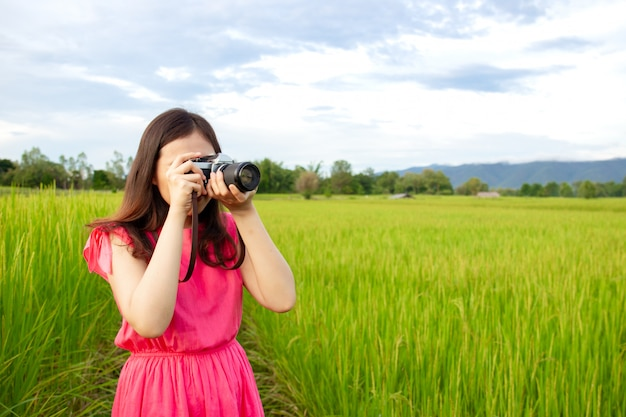 Портрет красивой молодой азиатской женщины в винтажном розовом платье фотографируя Premium Фотографии
