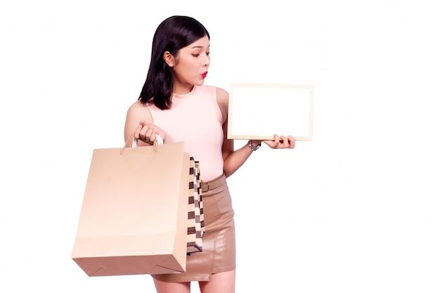 ショッピングバッグを運ぶと空の木製ホワイトボード、分離を保持している美しいアジアのスマートな女性をクローズアップ。白いシーンに分離されたアジアの女性の肖像画。買い物中毒のコンセプト。 Premium写真