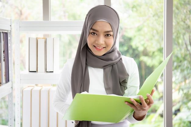 Азиатская мусульманская женщина пишет книгу в своем офисе Premium Фотографии