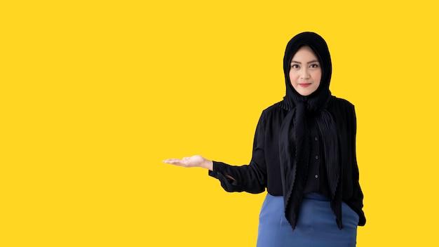 明るい黄色の壁でポーズスマートで美しいイスラム教徒の女性 Premium写真
